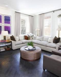 living-room-present-purple-accent-wall-and-l-shaped-sofa-design-also-awesome-gray-hardwood-floor-plus-round-ottoman-coffee-table-718x539
