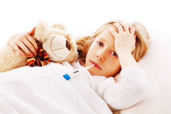 Little girl lying sick in her bed with her teddy bear.