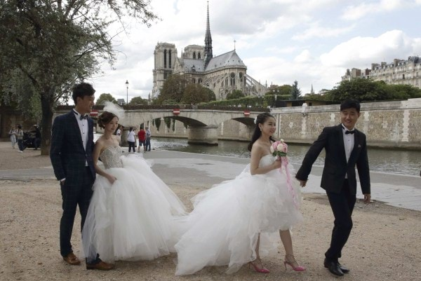 Two Chinese couples walk to attend their a pre-wedding photoshoots in front of the Notre-Dame Cathedral in Paris, France, August 28, 2015. As young Chinese become wealthier, they take abroad the tradition of taking their wedding photos days before they are married, rather than on their wedding day. Picture taken August 28, 2015. REUTERS/Philippe Wojazer