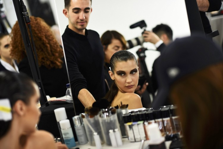 Model Bella Hadid has her make-up done inside ahead of a Dior fashion show in Woodstock