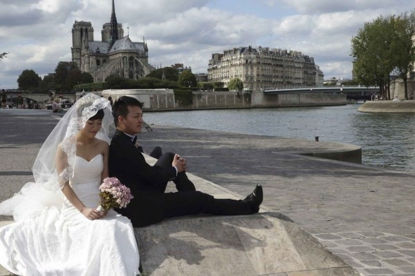 A Chinese couple poses during a pre-wedding photoshoot in front of the Notre-Dame Cathedral in Paris, France, August 28, 2015. As young Chinese become wealthier, they take abroad the tradition of taking their wedding photos days before they are married, rather than on their wedding day. Picture taken August 28, 2015. REUTERS/Philippe Wojazer
