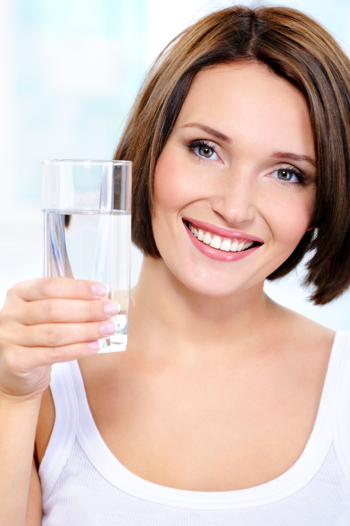 The beautiful smiling young girl holds a glass of clean water