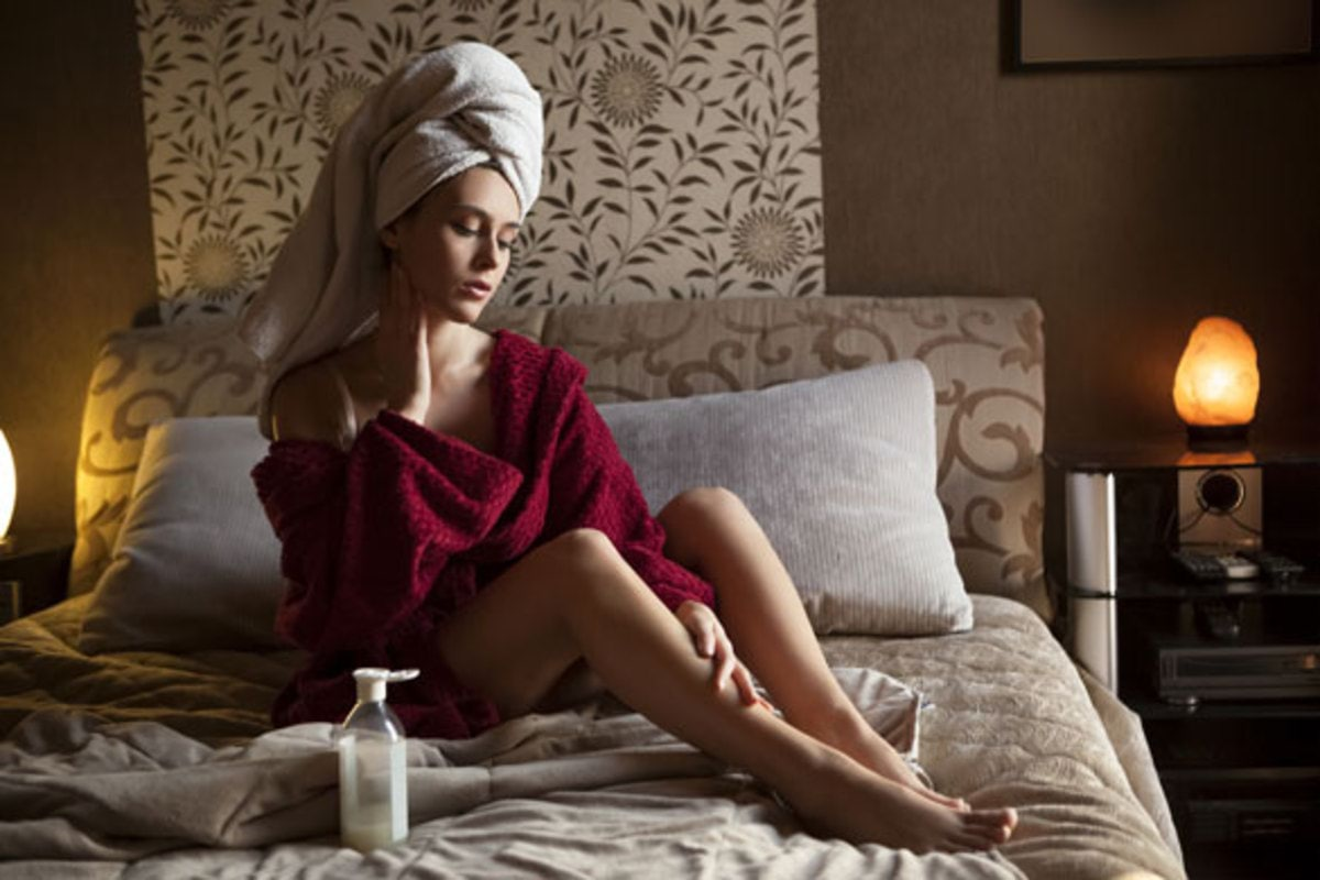 Beautiful-young-woman-in-bathrobe-applying-moisturizer-cream-early-in-the-morning
