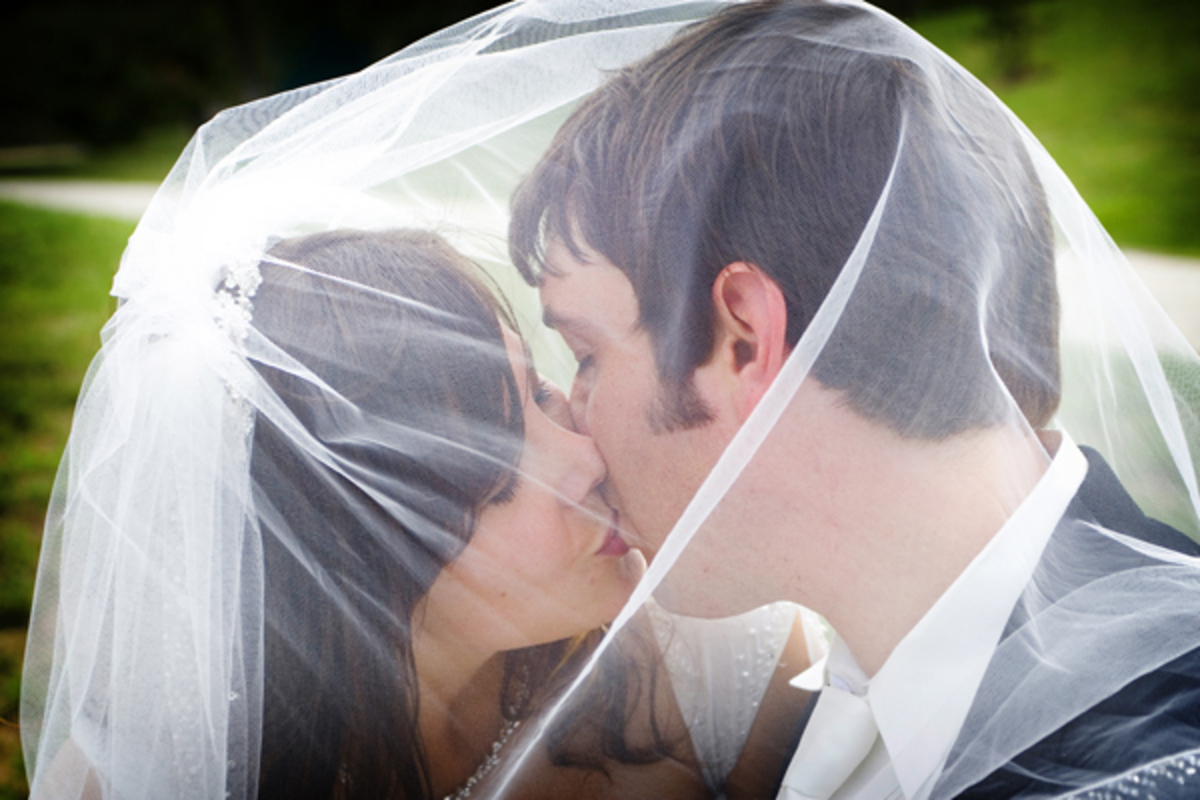 bride-and-groom-kissing-under-veil