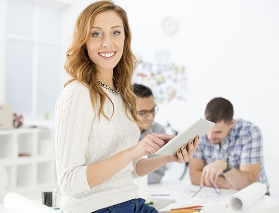 Cheerful architects discussing in office. Selective focus on female holding digital tablet with two people in background.