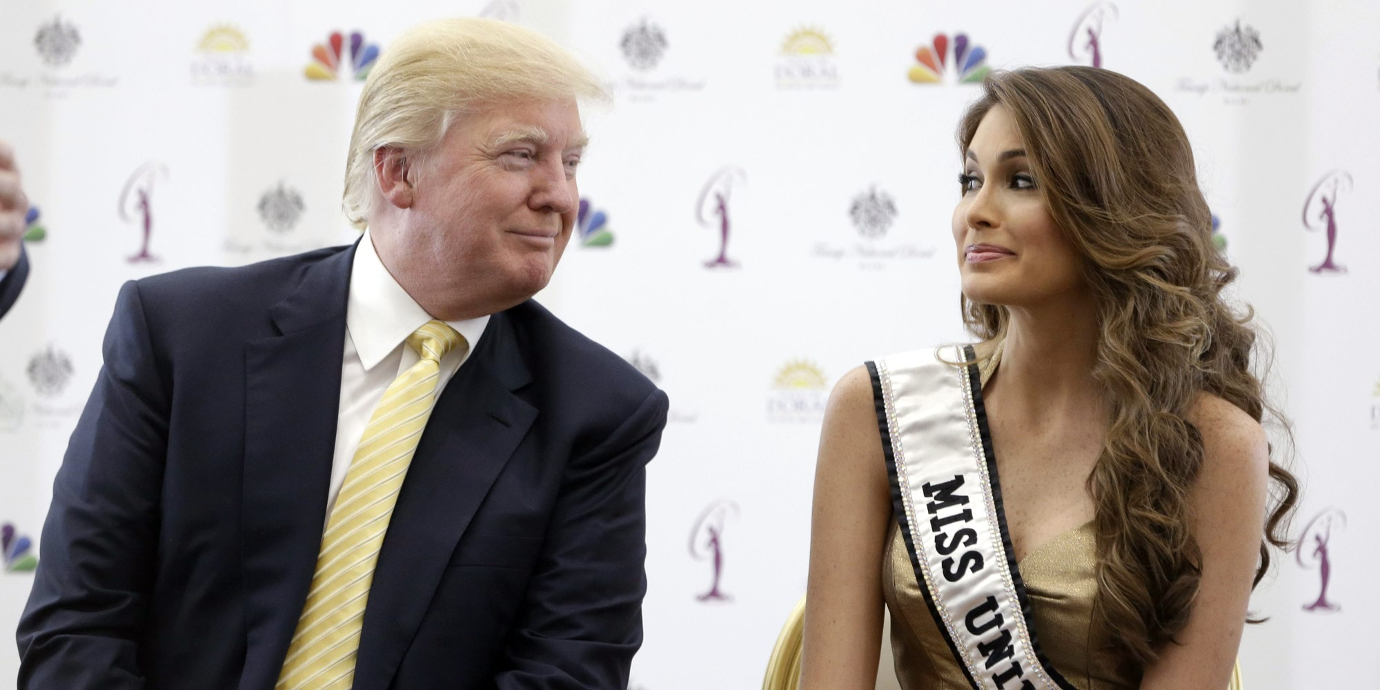Donald Trump, left, and Miss Universe, Gabriela Isler, of Venezuela, talk during a news conference, Thursday, Oct. 2, 2014, in Doral, Fla. Three of the last six Miss Universe titles have gone to Venezuelan contestants. This year's Miss Universe competition has a unique undertone: It will take place in South Florida, home to the largest number of Venezuelans in the U.S., the majority strongly against the current Venezuelan government. (AP Photo/Wilfredo Lee)