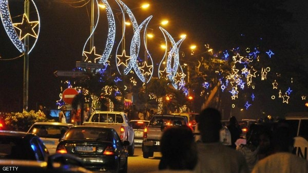 People walk down a street decorated with Christmas lights in the Plateau business district of Abidjan on December 23, 2013. AFP PHOTO/ SIA KAMBOU (Photo credit should read SIA KAMBOU/AFP/Getty Images)