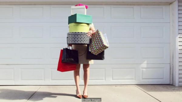 A woman stands in front of a garage door loaded down with shopping bags and hat boxes. You see only her legs and arms, her face is hidden behind the pile of boxes.
