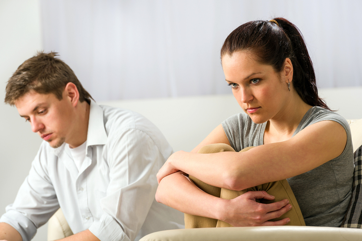 Unhappy couple sitting on couch silently after argument