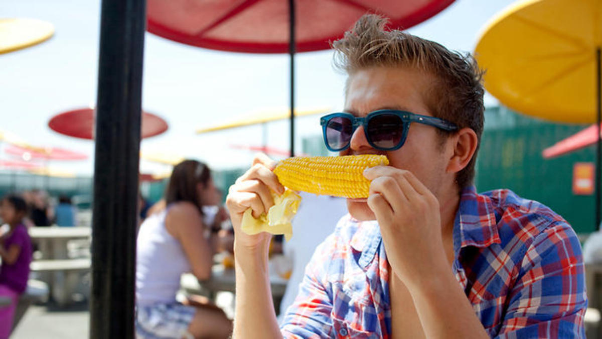 A young man wearing sunglasses eats corn on the cob on a hot summer day at an outdoor restaurant in Coney Island.