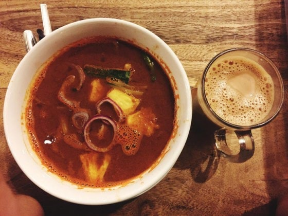 Directly Above Shot Of Asam Laksa And Teh Tarik Served On Wooden Table