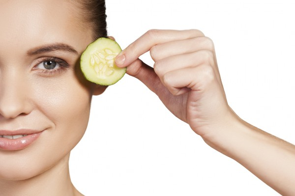 Cucumber spa. Cropped image of beautiful young woman holding piece of cucumber near her eye and smiling while isolated on white background